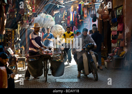 A Motor-scooter & laden bicycle in the colourful alleyways of the Souk, Medina, Marrakesh, Morocco, North Africa - Stock Photo