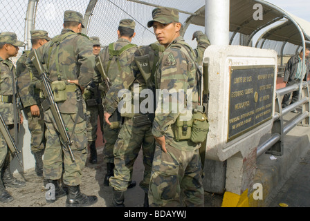 A small group of Mexican army soldiers walks along the Santa Fe Bridge between Ciudad Juarez and El Paso Texas - Stock Photo