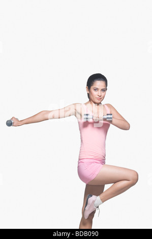 Portrait of a young woman exercising with a pair of dumbbells - Stock Photo