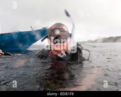 Indonesia Sulawesi Hoga Island Operation Wallacea diver on surface of water in pouring rain - Stock Photo