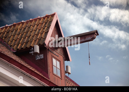Lifting construction on old house roof with small window and cloudy sky as background. Ancient architectural detail. - Stock Photo