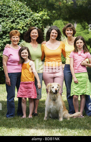 Family members standing with their dog - Stock Photo