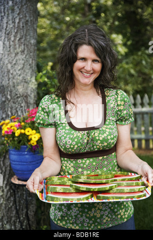Portrait of a mature woman holding a tray of sliced watermelon - Stock Photo