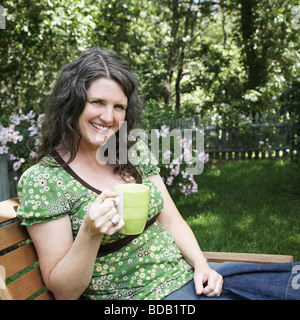 Portrait of a mature woman sitting on a chair and holding a tea cup - Stock Photo