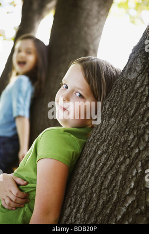 Side profile of a girl leaning against a tree trunk and smiling - Stock Photo