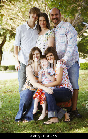 Portrait of a couple with their son and daughters in a lawn - Stock Photo