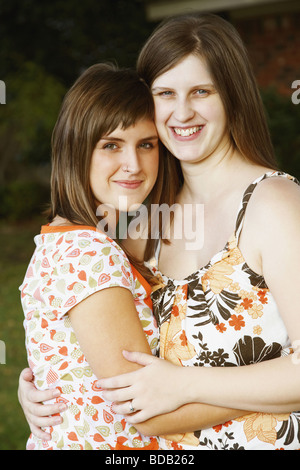 Portrait of a young woman hugging her sister and smiling - Stock Photo