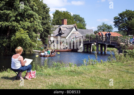 A WOMAN SKETCHING THE SCENE AT BRIDGE COTTAGE on the river Stour AT Flatford in Constable country. - Stock Photo