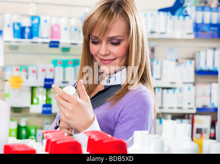 Portrait of blonde woman doing shopping in pharmacy - Stock Photo