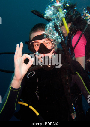 Indonesia Sulawesi Wakatobi National Park young student open water scuba diver giving OK hand signal - Stock Photo