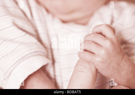 Baby's hand on mothers hand - Stock Photo