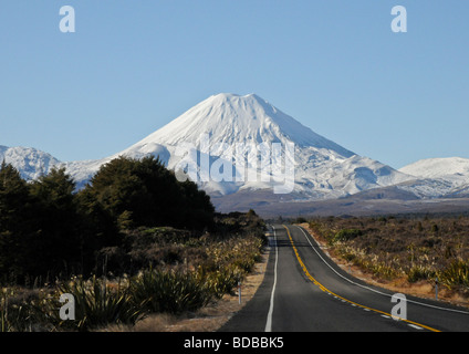 Panoramic view of main highway leading through forest into beautiful snow covered active volcanic Mount Ruapehu - Stock Photo