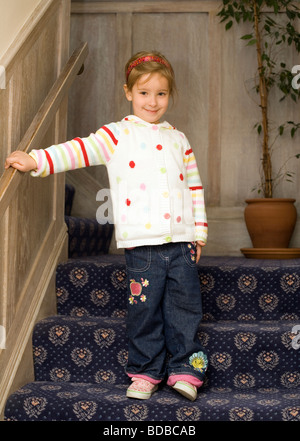 Pretty four year old girl on stairs  - London, England, UK, Europe - Stock Photo