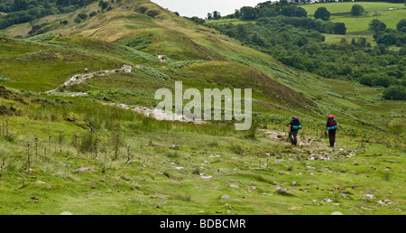 two male ramblers walking down from the  top of Conic Hill which over looks Loch Lomond in Scotland. - Stock Photo