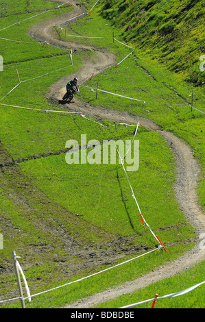A mountain biker rides a twisting downhill trail on a ski piste during summer in Pila in the Italian Alps - Stock Photo