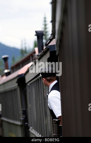 Skagway Alaska, The Brake Conductor on the White Pass and Yukon Route Railway leans out from between cars for a - Stock Photo