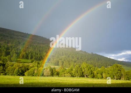 Double rainbow over Birch woodland and farmland in Glen Gairn. - Stock Photo