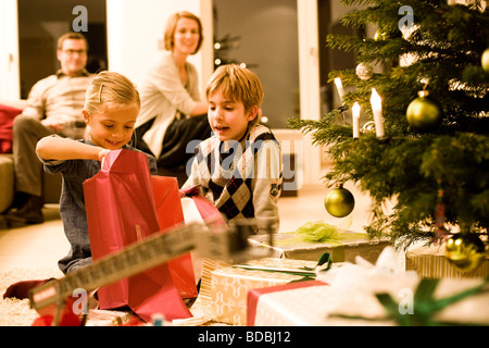 parents watching their children opening christmas presents on ...
