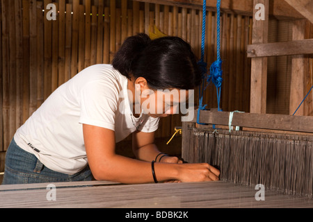 Indonesia Sulawesi Sengkang young woman adjusting loom in small local silk weaving workshop - Stock Photo