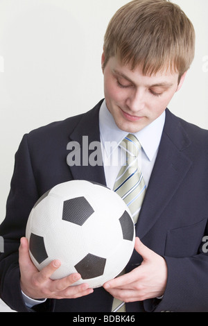 young businessman holding football - Stock Photo