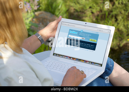 Female browsing social networking site Twitter with her laptop while relaxing in her garden - Stock Photo