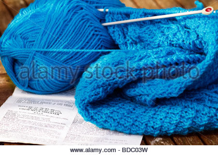 Knitting needles, blue yarn ball and open paper notebook on blue ...
