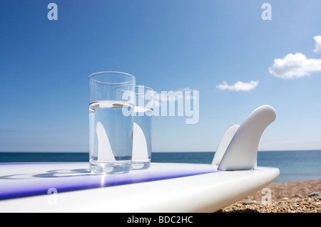 Surfboard on beach with two glasses of water - Stock Photo