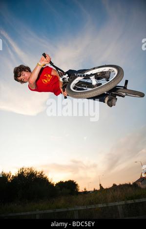 Teenage boy on trials bike at a skateboard park performing aerobatic stunts at dusk  Aberystwyth Wales UK - Stock Photo