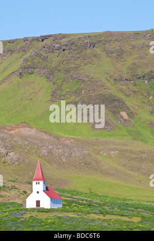 A Lutheran church sits alone on a hillside in Iceland - Stock Photo