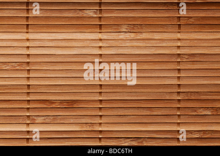 natural bamboo slatted mat background in brown tones - Stock Photo