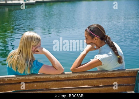 Two Tween tweens girls hang hanging out together Hispanic Caucasian junior high girls sit park bench and have a - Stock Photo