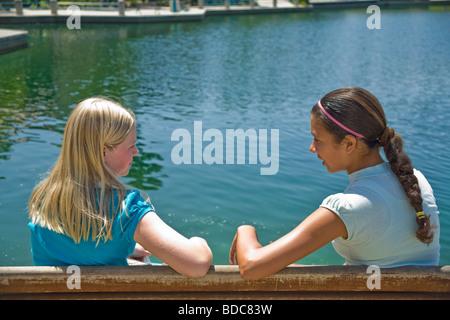 Two Tween tweens girls hang hanging out together Hispanic ethnic diverse multi Tween tweens girls sit park bench - Stock Photo