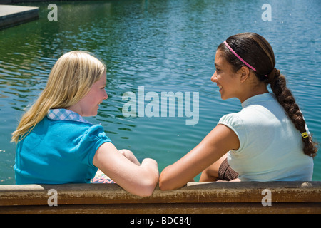 California Two Tween tweens girls hang hanging out together Hispanic Caucasian junior high girls sit on park bench - Stock Photo