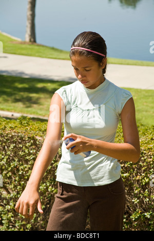 11-14 year old olds Junior high Hispanic/caucasian girl spraying sun screen on her arm. MR - Stock Photo