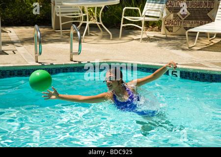 Junior high hispanic girl  11-13 year old olds catching ball in swimming pool. MR child children having fun - Stock Photo