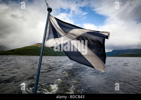 The Saltire flag of Scotland flying on the stern of a boat on Loch Lomond Scotland - Stock Photo