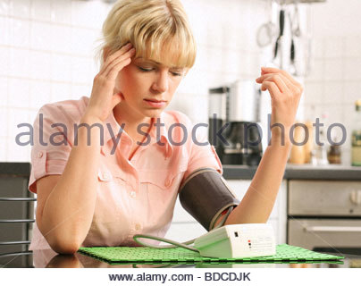 blond woman checking her blood pressure - Stock Photo
