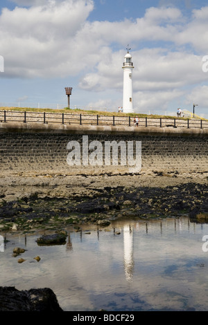 The old Roker cast iron lighthouse and brazier reflected in rockpool, Sunderland, north east England, UK - Stock Photo