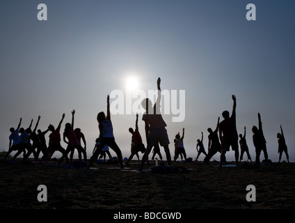 A Yoga Class stretches towards the sky on a beach in Guilford Connecticut USA - Stock Photo