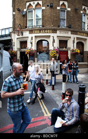 People gather outside The Globe pub at Borough Market. - Stock Photo