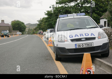 Two Irish Garda police cars parked on a no parking zone with no-parking traffic cones. - Stock Photo