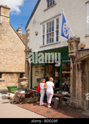 Window shopping at a small antiques shop in the Cotswolds town of Burford, Oxfordshire, England, UK - Stock Photo