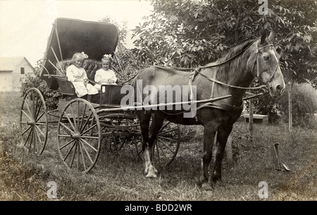 Little Twin Sisters Driving Horse Drawn Carriage - Stock Photo
