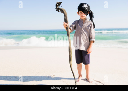 Boy in pirate costume standing on the beach - Stock Photo