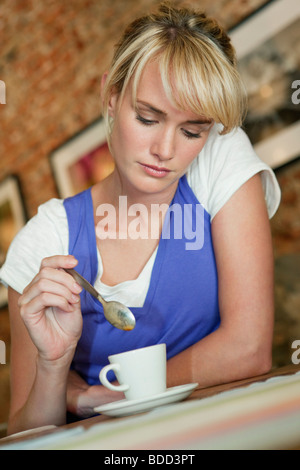 Woman stirring coffee in a cafe - Stock Photo