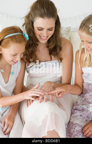 Bride showing her wedding ring to girls - Stock Photo