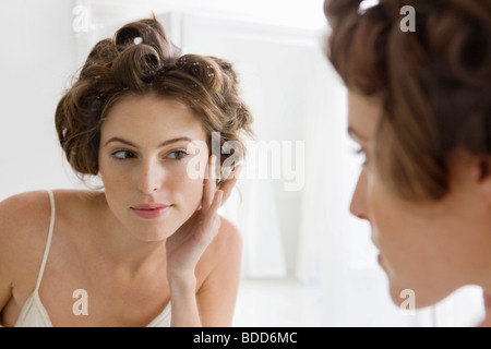 Woman examining her face in the mirror - Stock Photo