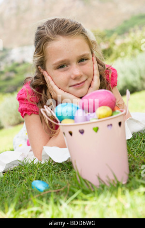 Container of Easter eggs in front of a girl - Stock Photo