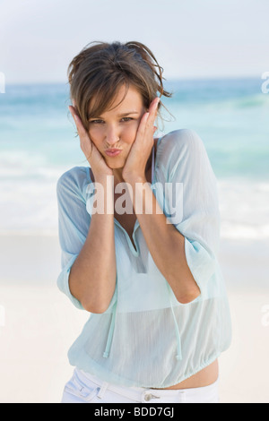 Woman making a funny face on the beach - Stock Photo