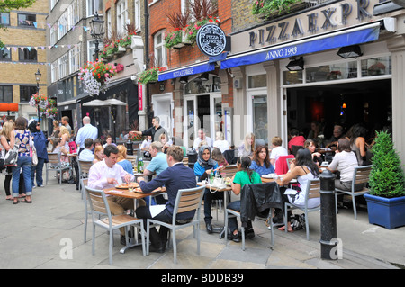 Pizza Express pizza restaurant with people eating out dining outdoors in St Christophers Place off Oxford Street - Stock Photo
